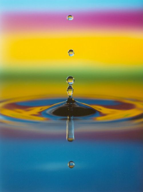 Splash-of-stream-of-water-drops-multihue-rainbow-backdrop-and-ripples-1-AJHD